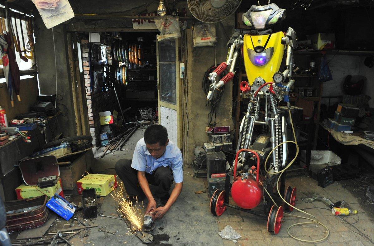 15. 49-летний механик Ву соединяет вместе детали своего нового робота в мастерской.