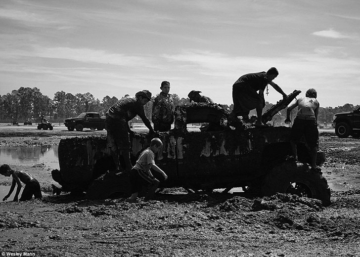Группа парней и мальчиков помогает толкать пикап, застрявший в грязи.