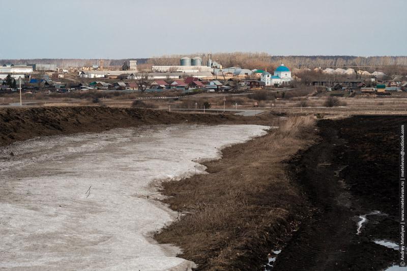 на переднем плане поле и снег, на заднем плане село Кочневское и церковь