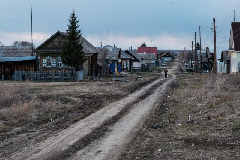 мужчина идет по грунтовой дороге в селе домой из магазина