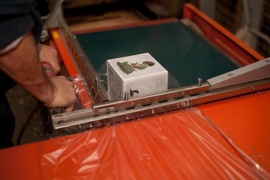 46. Финал сборки — термоусадка (заворачивание в плёнку). Коробка подаётся на ленте в специальную печ