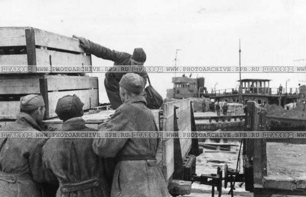 Оружие, привезенное с восточного берега, грузится на железнодорожные платформы узкоколейной дороги. 24 мая 1942 г.