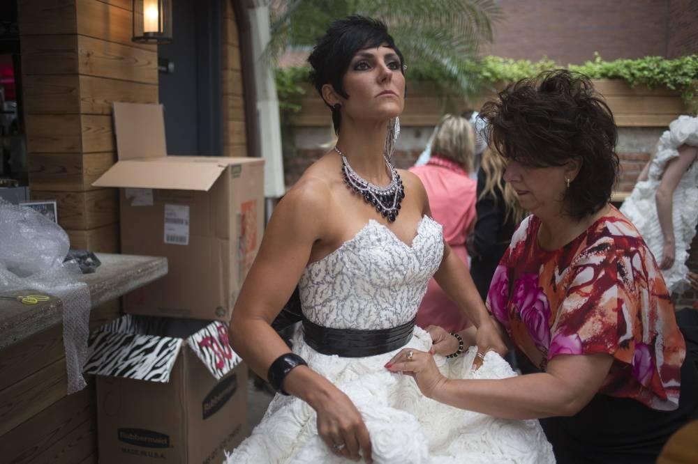 7. Дизайнер Julie Hass (справа) из Иллинойса поправляет платье на модели перед показом. Платье сдела