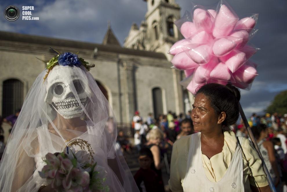 Продавщица сладкой ваты непринужденно принимает заказ у участницы маскарада. (AP Photo/Esteban F