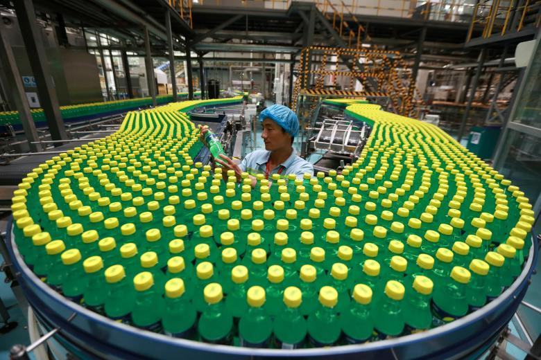 Работник осматривает алюминиевые слитки на экспорт в порту в Циндао в провинции Шаньдун.