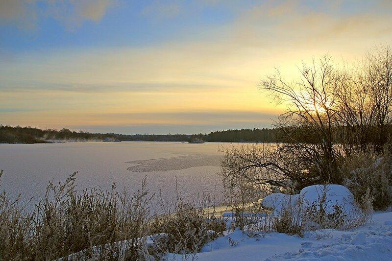Зимний пейзаж озера Жуково (Кирово-Чепецк): покрытая льдом гладь озера, закатное солнце прячется среди ветвей дерева