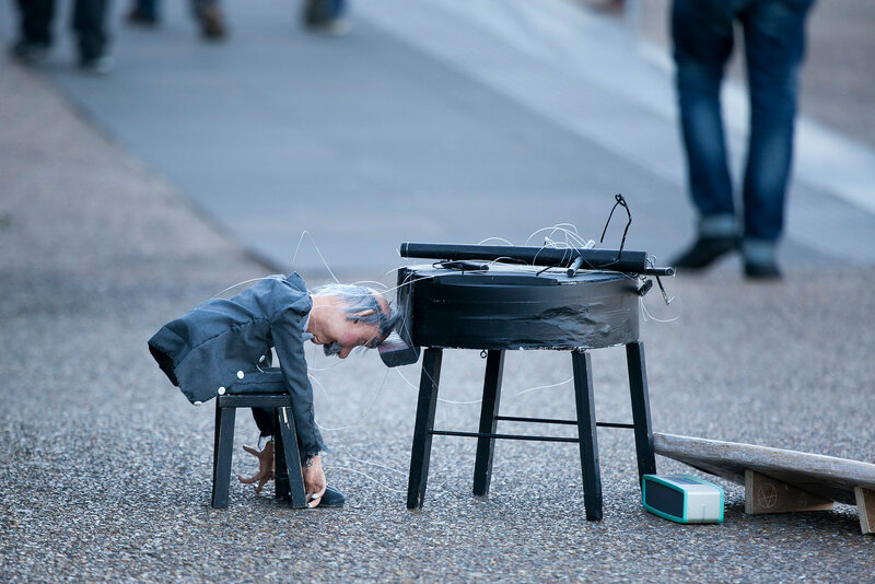 Puppet pianist leaned his forehead against the toy piano, standing on the road