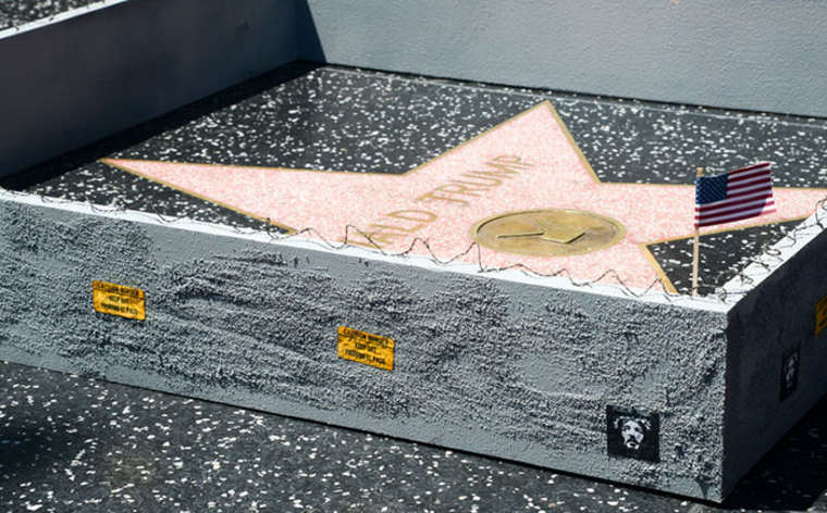 An artist erects a miniature wall around the star of Donald Trump