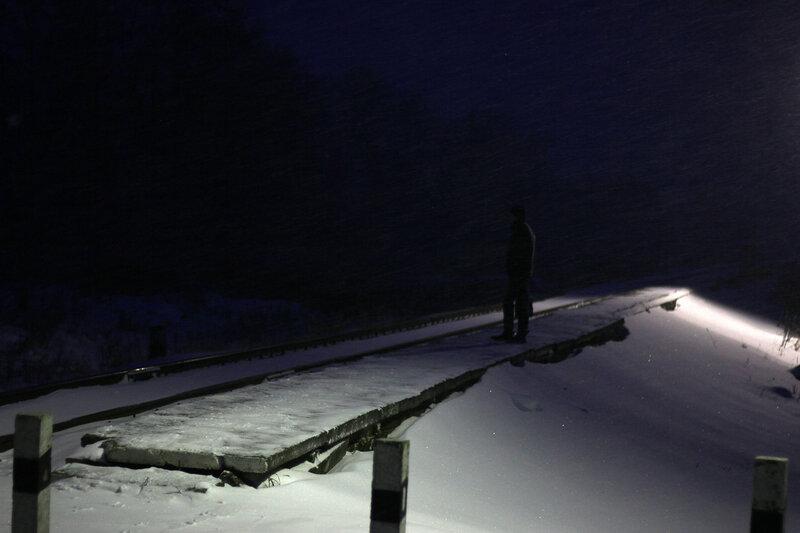 Ночной пассажир в ожидании поезда на платформе Вазуза под снегом
