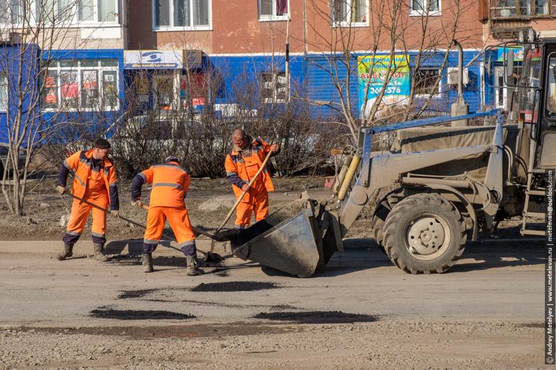 фотография дорожных рабочих в оранжевых одеждах ремонтирующих дорогу