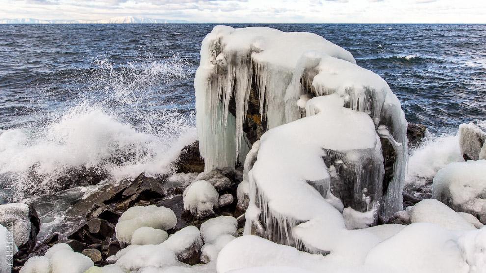 16. Бушующий Байкал окутывает брызгами и деревца стоящие недалеко от берега.