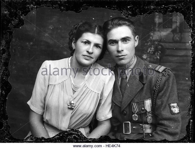 Cuplu Sergent major în ţinută model 1934/40, cu ecusonul Diviziei Tudor Vladimirescu. Imaginea este luată probabil imediat după război, deoarece poartă furajera (eghiletul simplu) de unitate decorată. Pe piept poartă Medalia sovietică Pentru Victoria în M