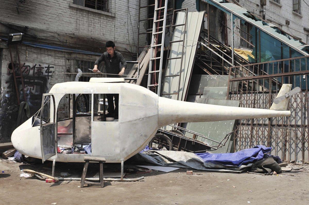 22. Гао Ханьцзе устанавливает лопасти на свой самодельный вертолет.