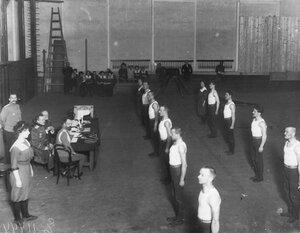 Группа гимнастов, членов Общества телесного воспитания Богатырь перед экзаменационной комиссией в гимнастическом зале 2-го Кадетского корпуса. 1912