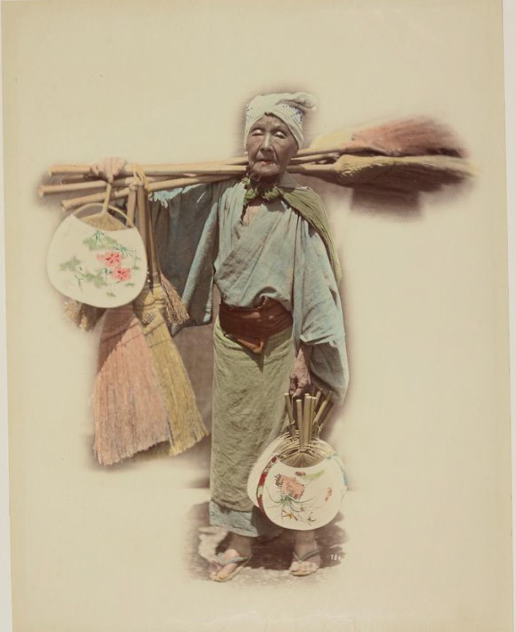 Старая женщина продает метлы и веера