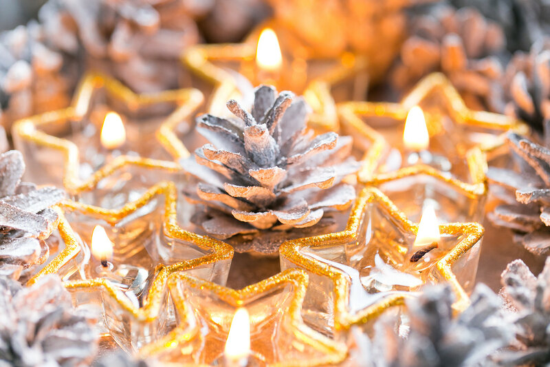 Christmas. Christmas card with glowing small candle and fir cones on old wooden background.