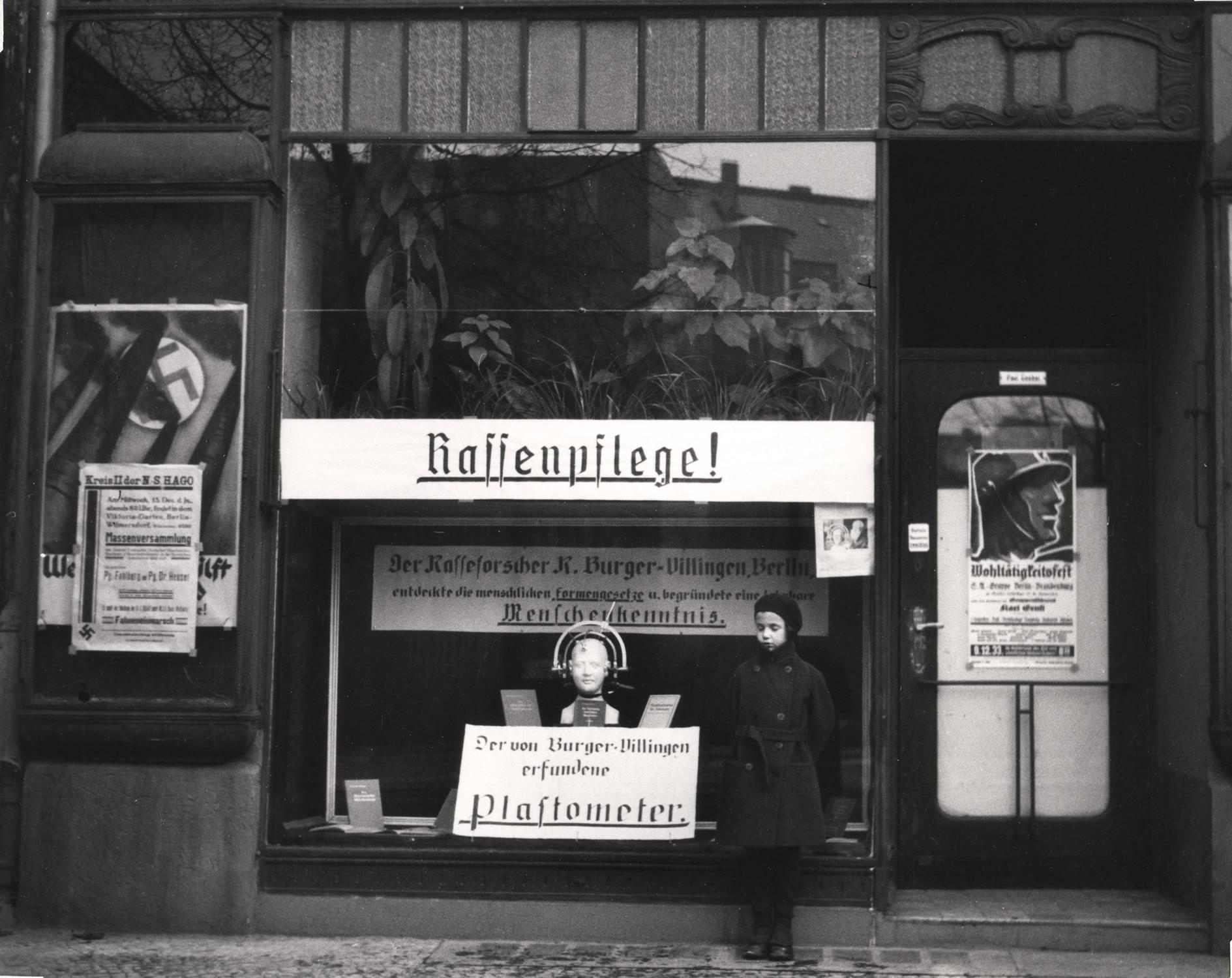 1933. Дочь Вишниака Мара позирует перед магазином, специализирующимся на инструментах, измеряющих разницу в размерах между арийскими и неарийскими черепами. Берлин