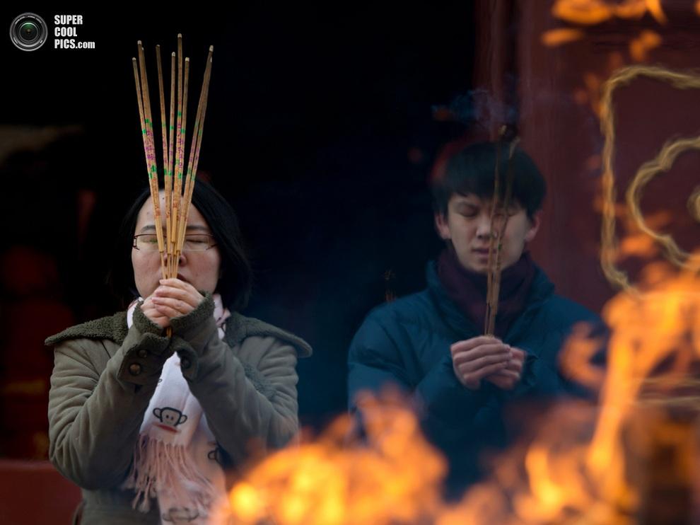 Прихожане молятся в буддийском храме Юнхэгун, Пекин, Китай. (Ed Jones/AFP/Getty Images)