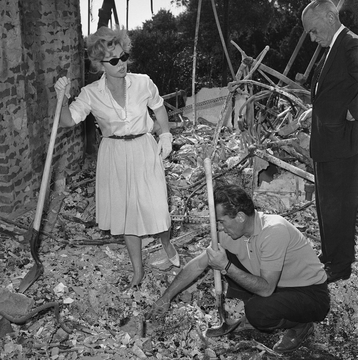 Жа Жа Габор и ее друг Роберт Стрейл копаются в обломках ее сгоревшего особняка в Бел-Эйр за 275 тыся