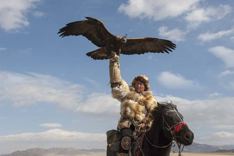 A Kazakh eagle hunter showing off his golden eagle at the Golden Eagle Festival.