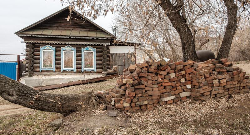 деревянный дом и гора кирпичей перед ним