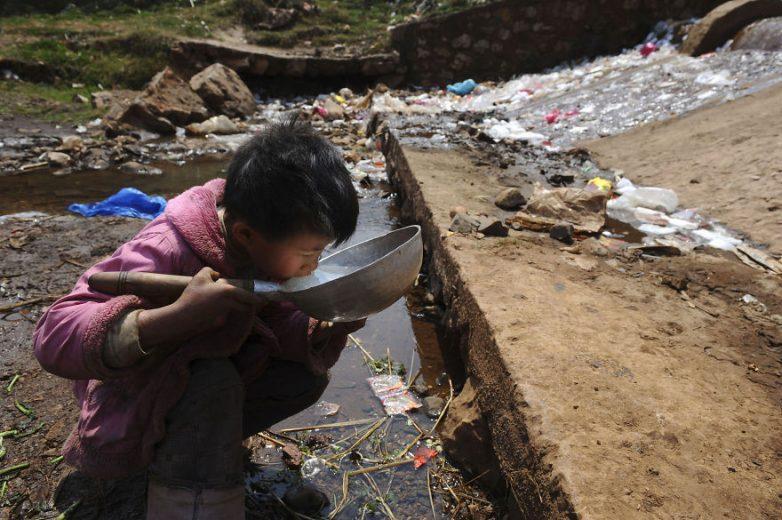 2. Ребёнок пьёт воду из грязного ручья в Фуюань, провинция Юньнань