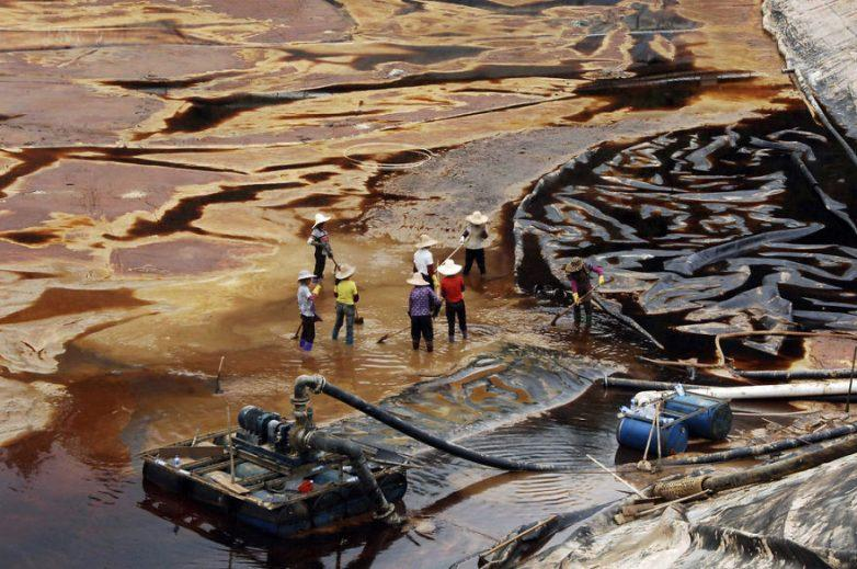 27. Рабочие пытаются очистить водный объект от нефтяного разлива, провинция Фуцзянь, Китай