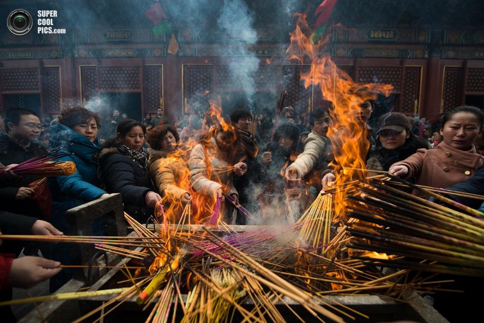 Прихожане поджигают благовонные палочки в храме Юнхэгун,Пекин.(ED JONES/AFP/Getty Images)