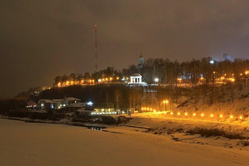 Ночной зимний вид с реки на Александровский сад с подсвеченной ротондой, улицу Пристанскую и нижнюю прогулочную набережную. Сзади на фоне телевышка и колокольня Преображенской церкви