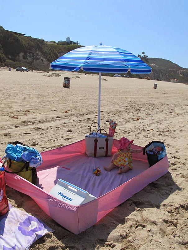 С помощью натяжной простыни можно оградить ребенка от песка на пляже