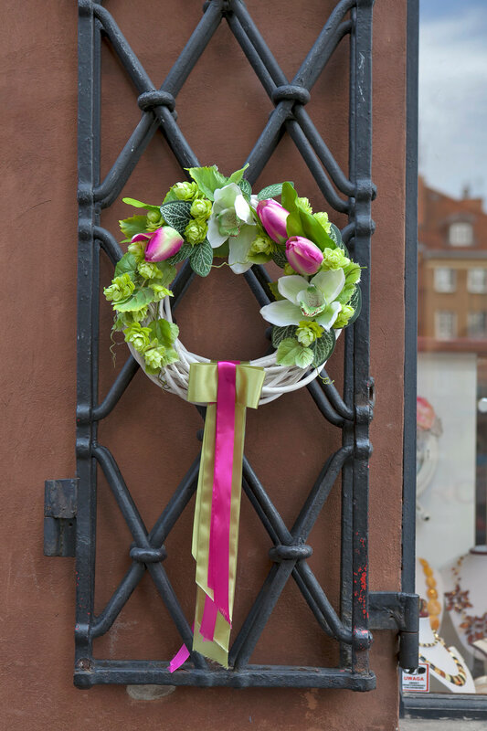 the Wreath of flowers with ribbons on the door in a cafe in Warsaw, Poland