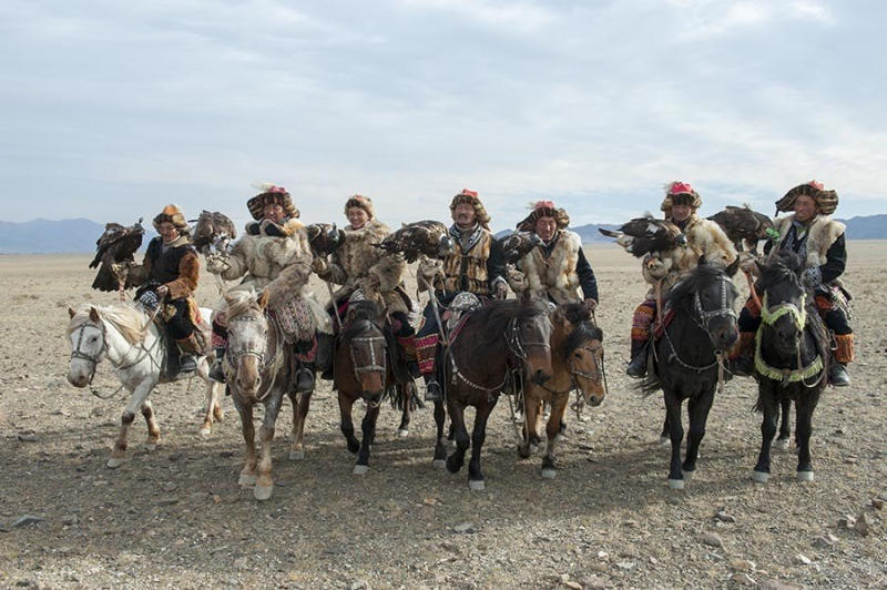 A group of Kazakh Eagle hunters and their golden eagles posing after arrival at the Golden Eagle
