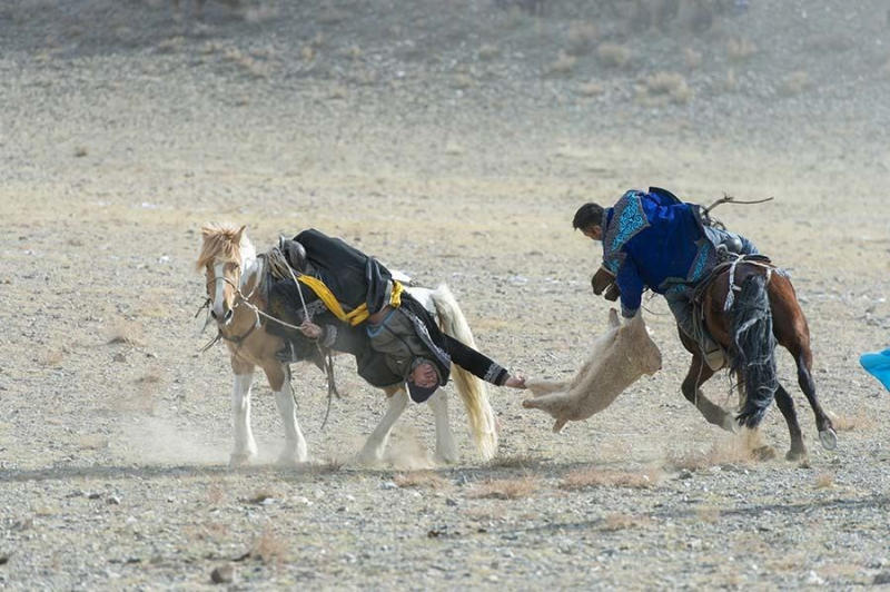 The Kukhbar competition is a traditional horseback riding game where the riders fight over a goat sk