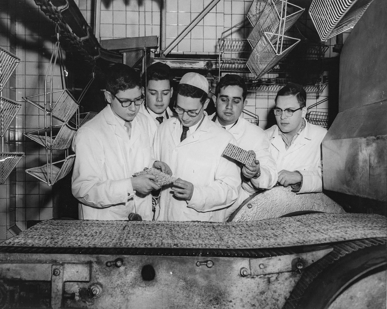 1950-е. Ученики ешивы разглядывают мацу, выходящую из печи в заводском цеху