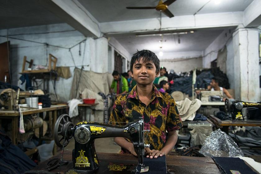 Работа этого мальчика — крепить этикетки на джинсы.