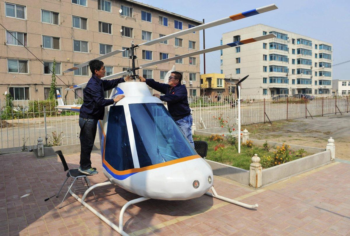 13. 55-летний кузнец Тянь Шэнин (справа) поправляет лопасть своего самодельного вертолета.