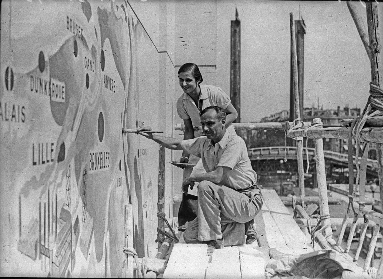 Последние штрихи краски на фасаде Павильона Туризма делают г-н и г-жа Пирр Гауди (2 июня 1937)