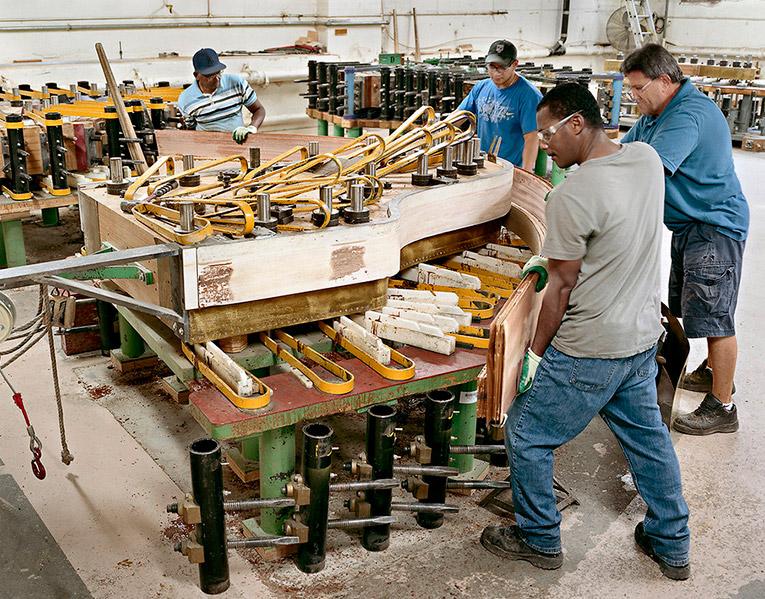 Бригада рабочих закрепляет ее в специальном прессе с помощью тисков и хомутов, для придания бок