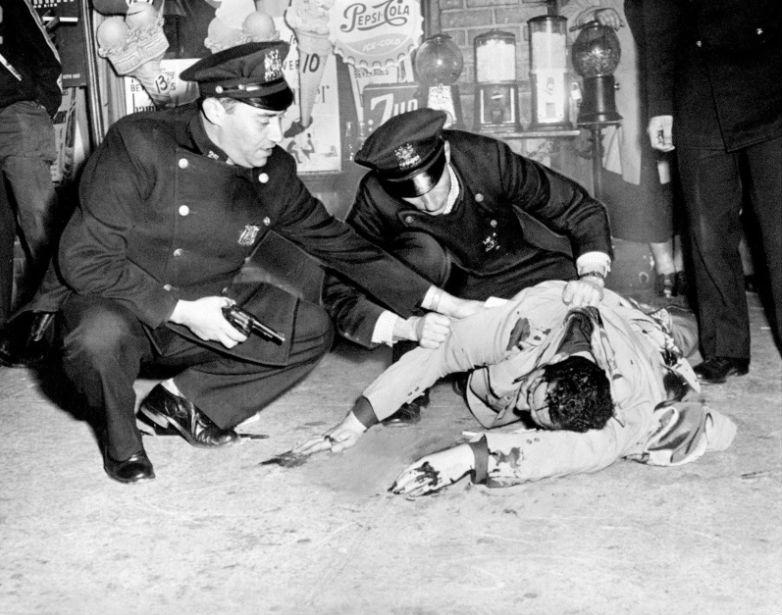 Полицейские проверяют подозреваемого в ограблении после того, как он сопротивлялся аресту, 1953 год.