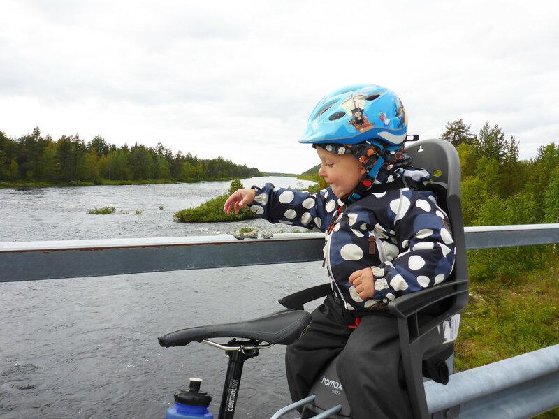 ребенок в велокресле кидает камни в воду с моста