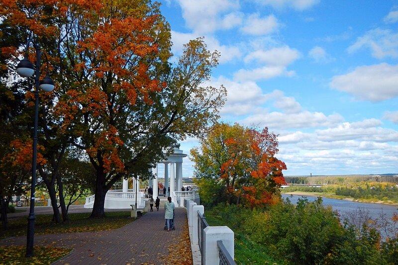 осенняя набережная в Александровском саду: красные клёны, усыпанная листьями дорожка, ротонда на высоком берегу и облака