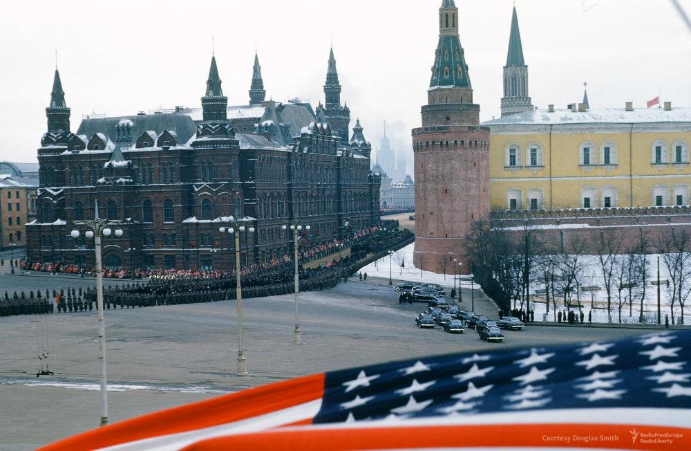 Камера переключается на Красную площадь: перед мавзолеем Ленина толпятся сотни официальных лиц. Член
