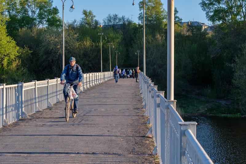 велосипедист и люди на Пешеходном мосту через Исеть