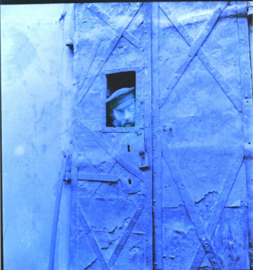 Еврей выглядывает через железную дверь во время антисемитского погрома