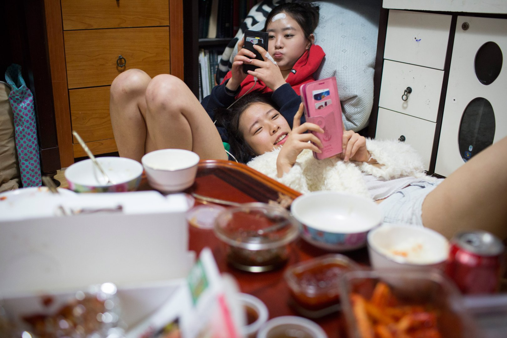 Кьёнг-ок и Сара коротают время, глядя в телефоны, после того как поужинали дома у Кьёнг-ок, взяв еду