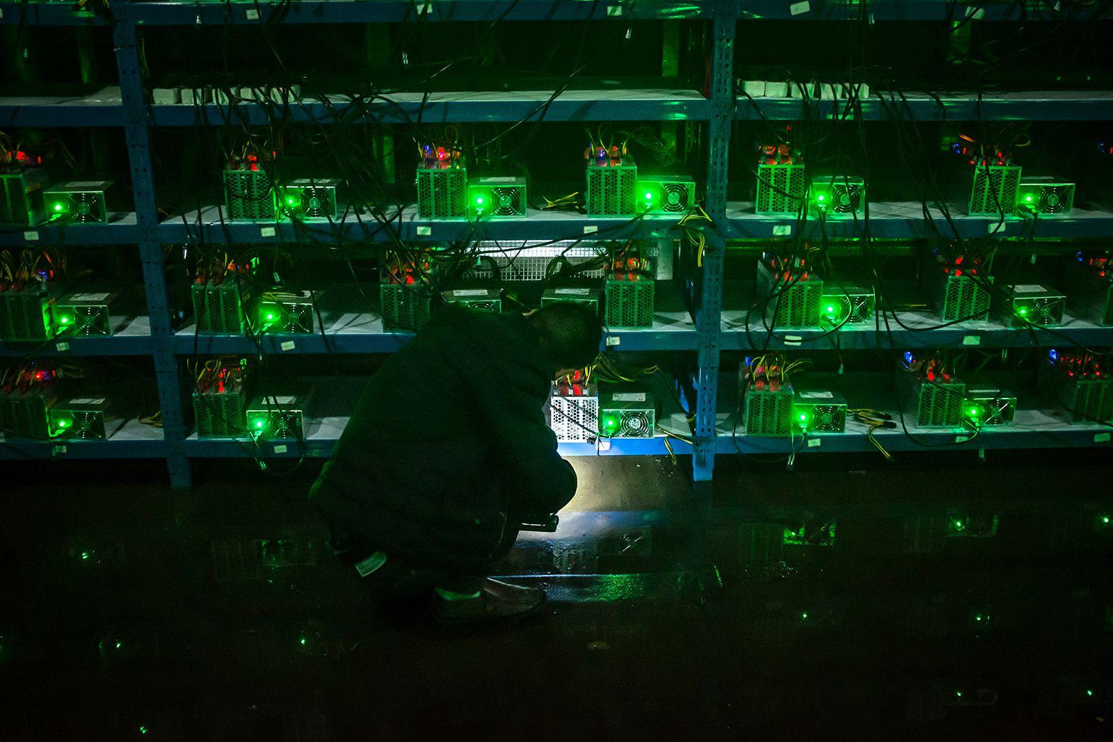 Майнер в ночную смену проверяет исправность мультифункциональных машин.