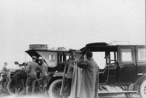 Водитель осматривает мотор в автомобиле на стартовой площадке