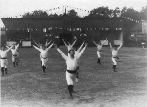 Группа членов Гимнастического общества Пальма делает упражнения на спортивной площадке