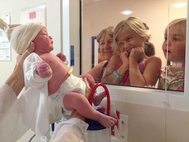 Девочкам показывают новорожденную сестренку.