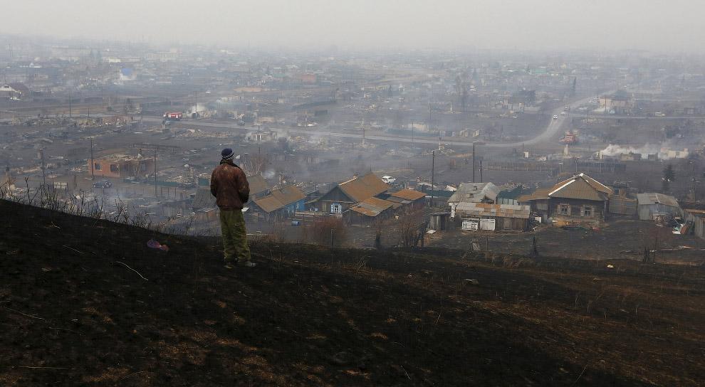 11. Хозяин разбирает вещи в своем сгоревшем доме, Хакасия, 13 апреля 2015. (Фото Ilya Naymushin   Re